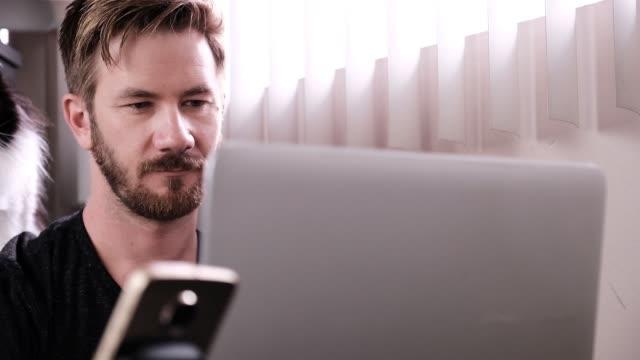 stockvideo's en b-roll-footage met een man en zijn kat werk vanuit huis - alleen één mid volwassen man