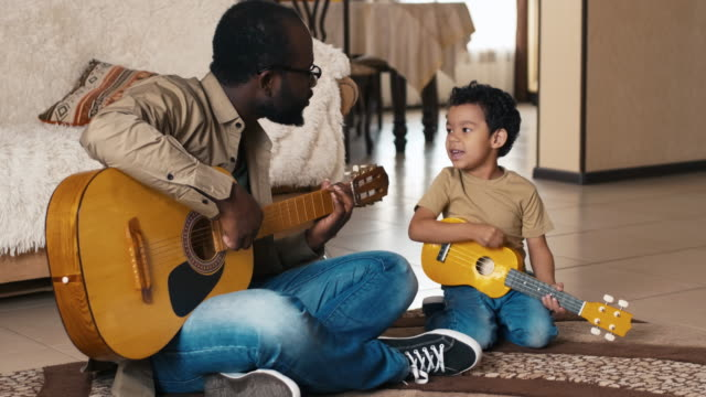 Man and his son playing guitars and singing song African American man sitting on carpet at home near his biracial son, both playing guitars and singing song guitar stock videos & royalty-free footage