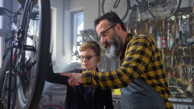 SLO MO Man and his young son checking the chain on a bike in the workshop