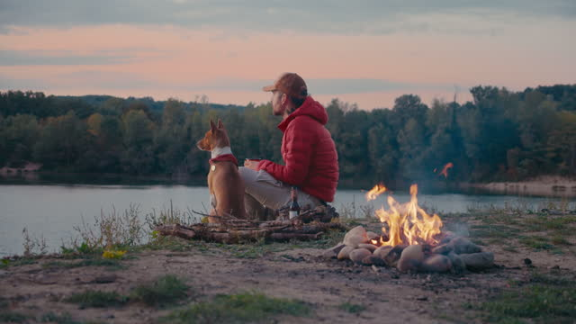 Man and pet dog rest next to campfire on hike trip