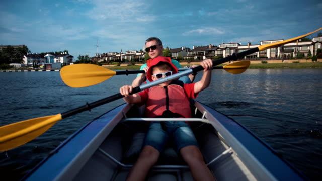 man och son kajakpaddling - flod vatten brygga bildbanksvideor och videomaterial från bakom kulisserna