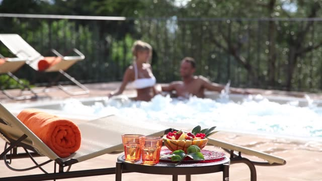 man and woma chatting in a hot tub with beach chairs and fruit on a coffee ta video
