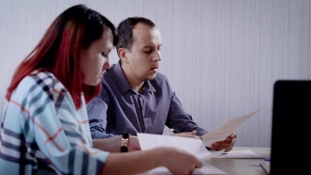 vidéos et rushes de homme et femme sont clients d'une entreprise de l'agent immobilier sont assis dans une service clientèle et lisant journaux - notaire