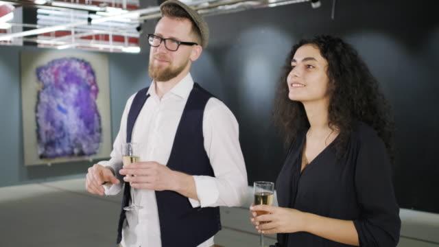 男女がギャラリーのオープニングでシャンパンを飲み、写真を見ている - 展示点の映像素材/bロール