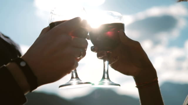 Man and woman are drinking wine in glasses against the blue sky video