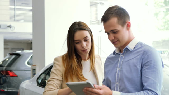 Man and woman are looking on the tablet in the car dealership video