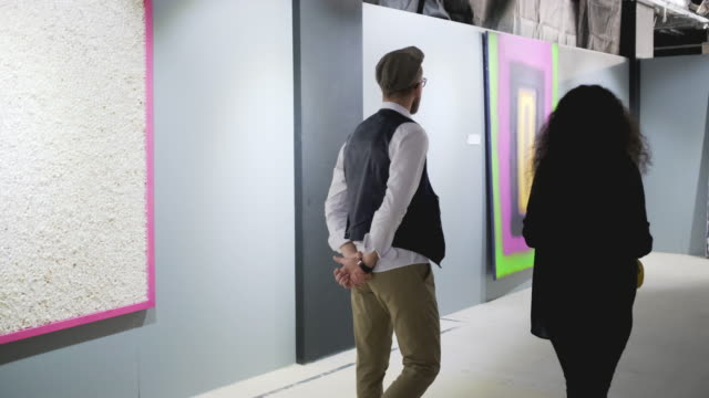 Man and woman are moving in hall of art gallery and talking about pictures