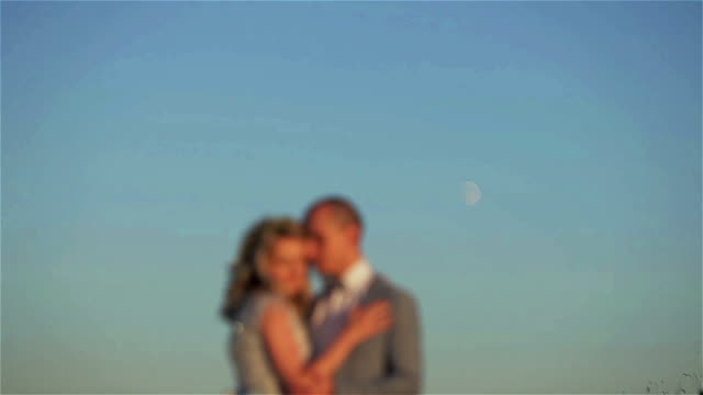 Man and woman blurred stand embracing at moon in sky background. Couple unfocused silhouetted kiss holding at shining lunar disk shining in clear sky space. Planning pregnancy moon phase cycles fertility video