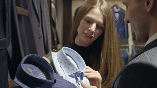 Man and Woman Choosing Shit in Menswear Store Close up of happy woman and man standing in aisle of menswear boutique and choosing between two stylish shirts button down shirt stock videos & royalty-free footage