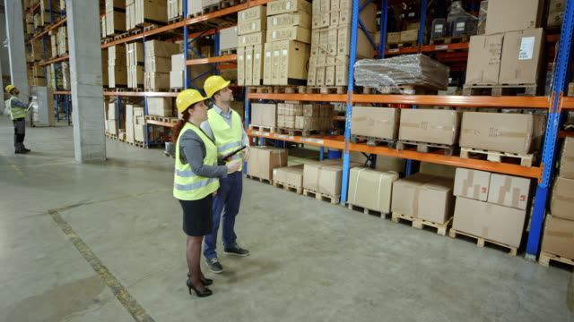 CS Man and woman discussing the storage area in the warehouse video