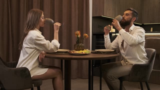 man and woman drink sparkling champagne at home kitchen. date at home after a hard day at work