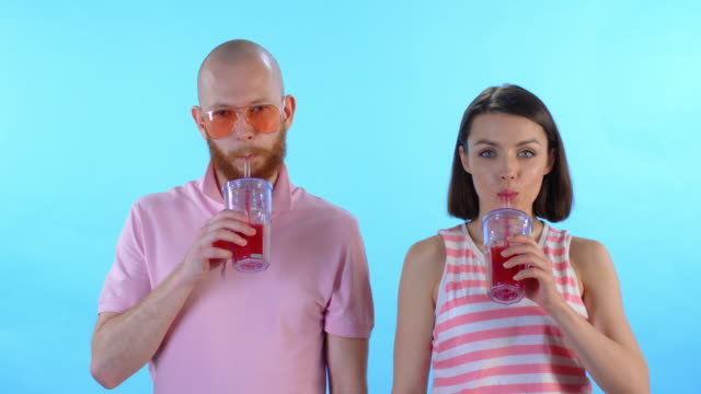 Man and Woman Drinking Juice and Smiling