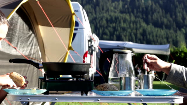 Man and woman eating breakfast in camping video