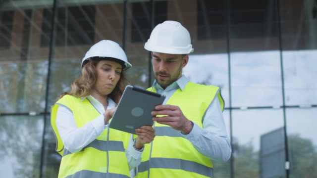 Man and Woman Engineers Have Conversation and using Tablet Computer on Construction Site. Glass Building on Background. video