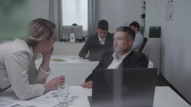mann und frau flirten bei der arbeit miteinander - unterordnung stock-videos und b-roll-filmmaterial