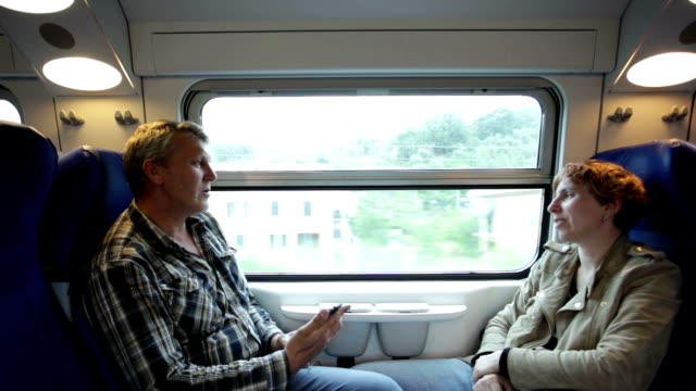 man and woman go by  train sitting  friend opposite video