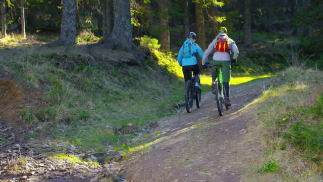 SLO MO Man and woman going uphill on mountain bikes video