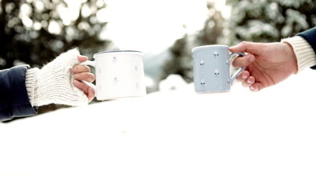 stockvideo's en b-roll-footage met man en vrouw handen in het breien van wanten met kopjes hete thee op winter forest gl - family winter holiday