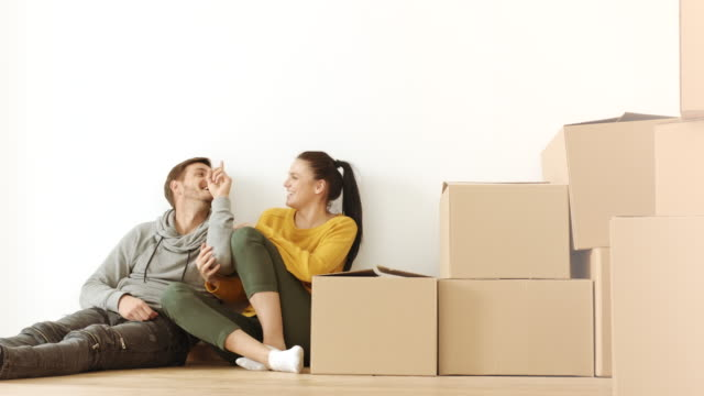 Homme et femme s'amuser dans la salle remplie de boîtes en carton - Vidéo