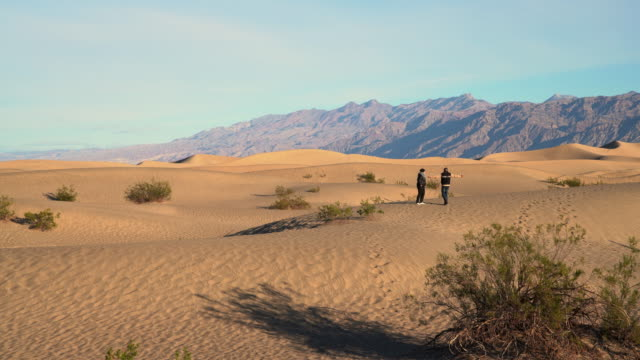 Man and woman hiking on sand dunes at Mesquite Flats, Death Valley, California.