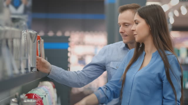 A man and woman hold in their hands an electric kettle in a store choosing before buying in appliances store A man and woman hold in their hands an electric kettle in a store choosing before buying in a store. department store stock videos & royalty-free footage
