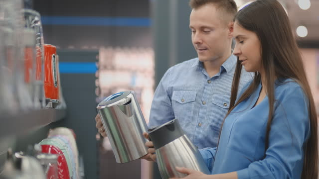 A man and woman hold in their hands an electric kettle in a store choosing before buying in appliances store A man and woman hold in their hands an electric kettle in a store choosing before buying in appliances store. department store stock videos & royalty-free footage