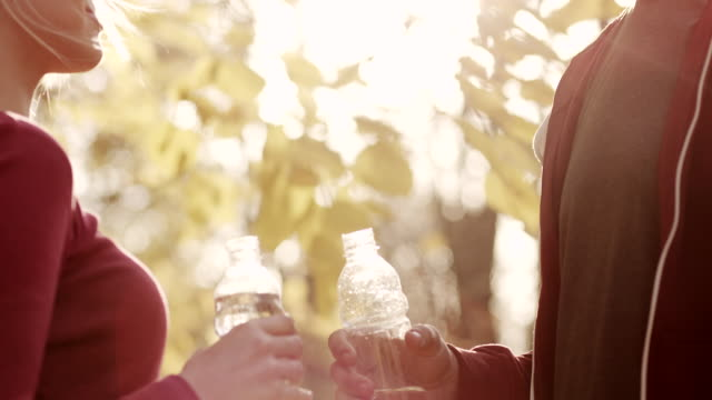 Man and woman holding a bottles of water video