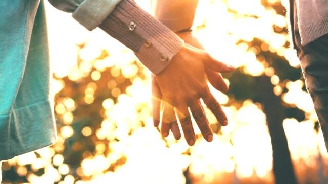 mann und frau, die hand in hand an sonnigen tag - hände halten stock-videos und b-roll-filmmaterial