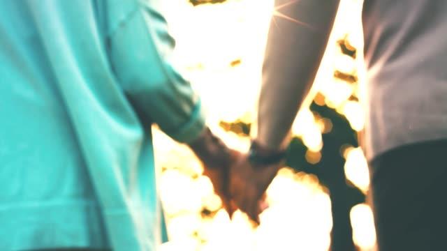 man and woman holding hands during sunny day - podświetlony filmów i materiałów b-roll
