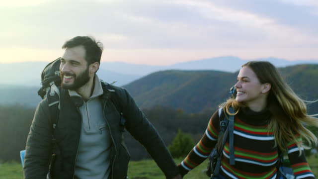 man and woman holding hands while hiking on mountain - турист с рюкзаком стоковые видео и кадры b-roll