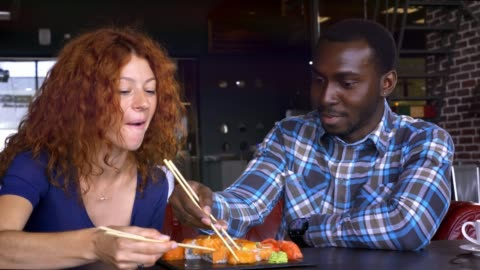 mężczyzna i kobieta w kawiarni jedzą sushi i komunikują się. - data filmów i materiałów b-roll