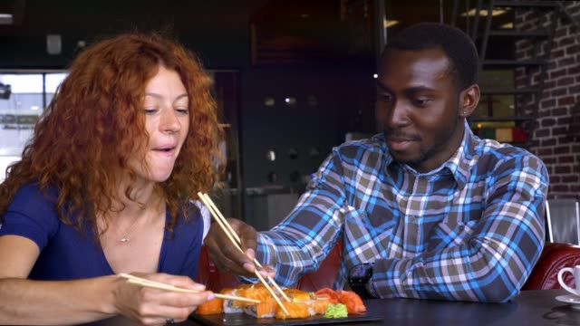 vídeos y material grabado en eventos de stock de hombre y mujer en un café, comen sushi y comunican. - sushi