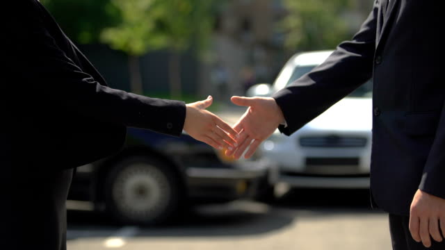 Man and woman in business suits shaking hands after meeting, successful deal