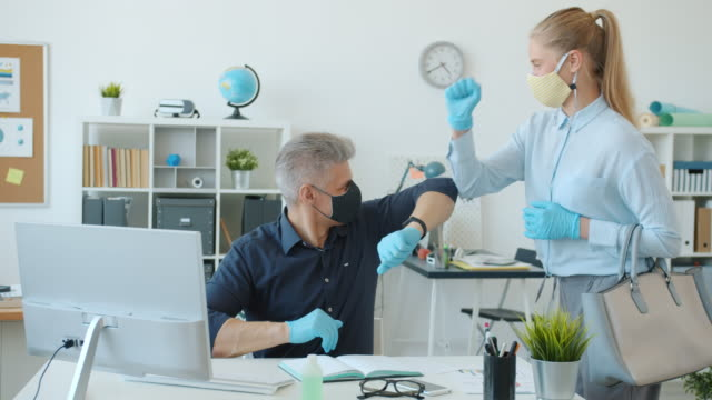 Man and woman in face masks office workers doing elbow high-five at work during pandemic video