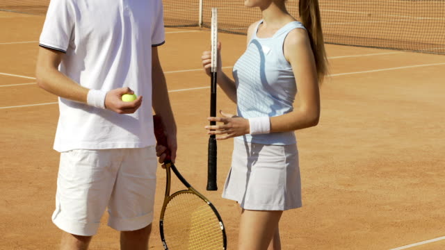 Man and woman in sportswear standing on tennis court and flirting, sports hobby Man and woman in sportswear standing on tennis court and flirting, sports hobby charming stock videos & royalty-free footage