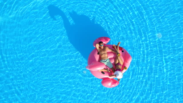 aerial: man and woman in swimsuits laying on fun pink inflatable flamingo float - località turistica video stock e b–roll