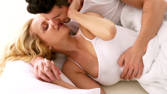 Man and woman kissing in bed, waking up video