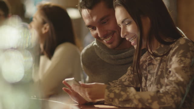 Man and woman laugh while using a smartphone and having a good time in a bar. video