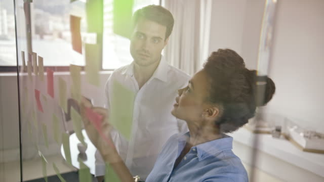 man and woman looking at notes - post it video stock e b–roll