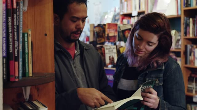Man and Woman Looking Through a Book in Bookstore