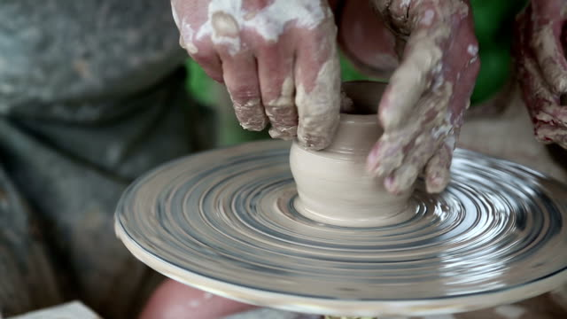 Man and woman makes a pot on pottery wheel video