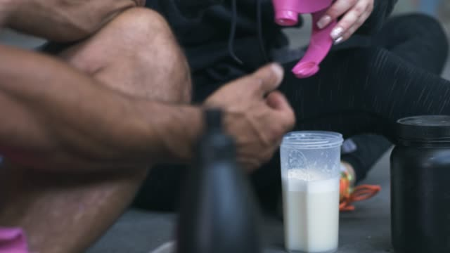 Man and Woman Making Protein Shake after Exercise A man and a women are mixing a protein shake after their exercise inside an abandoned warehouse. Shot in 4K resolution. protein stock videos & royalty-free footage