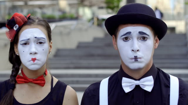 Man and woman mime play their facial expressions Two funny mimes play a scene. Girl and guy gesticulates their facial expressions. Young amateurs earn money showing people small funny scenes at urban streets. greasepaint stock videos & royalty-free footage