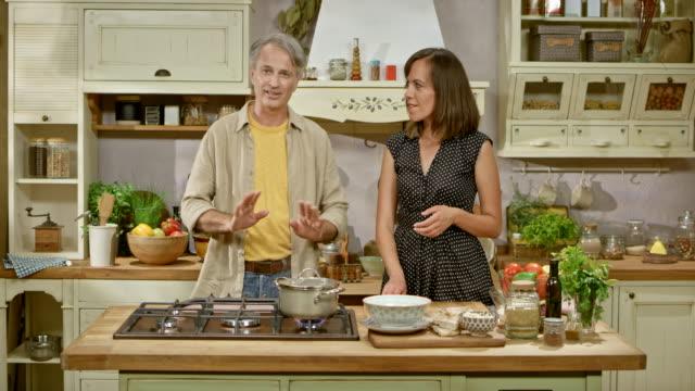vidéos et rushes de ld homme et femme sur une table de cuisson montrent parle d'ingrédients et la préparation des aliments - montrer