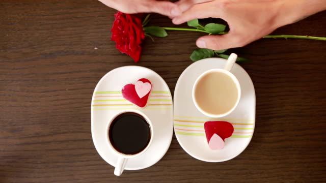 カフェでデートする男女コーヒーとケーキを飲む花を与える - ソーサー点の映像素材/bロール