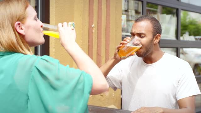 mężczyzna i kobieta w porze lunchu data okrzyki i konkurować, aby zakończyć ich napoje - scone filmów i materiałów b-roll