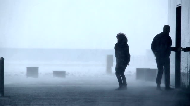 man and woman ouside building in raging blizzard snowstorm, Reykjavik, Iceland video