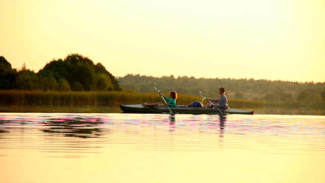 Man and woman paddling boat synchronously. Team-building, sport video