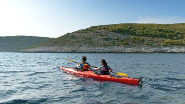 vídeos de stock, filmes e b-roll de ts de homem e mulher remando em sua mar caiaque ao longo do litoral, em um dia ensolarado - caiaque