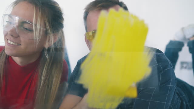 man and woman paint wall with different colors smile kissing